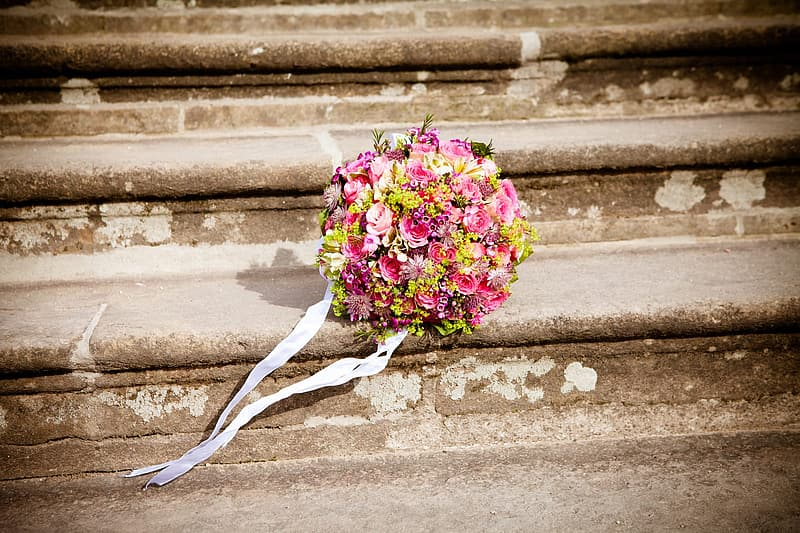 Pink and yellow petaled flowers bouquet in the stairs