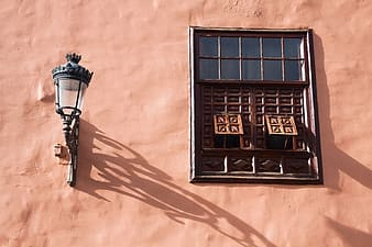 Sconce lamp beside black and brown windows