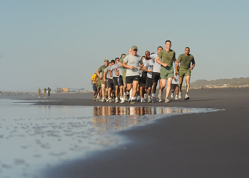 Group of men running along the beach