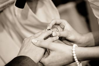 Grayscale photography of person holding silver-colored wedding ring