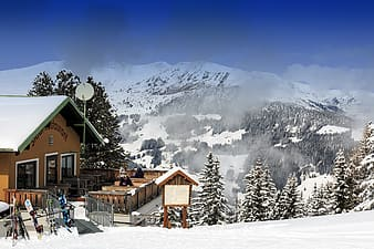 Brown wooden house on snow covered ground near snow covered mountain during daytime