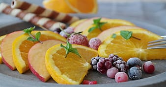 Sliced orange fruit and grapes on brown wooden chopping board