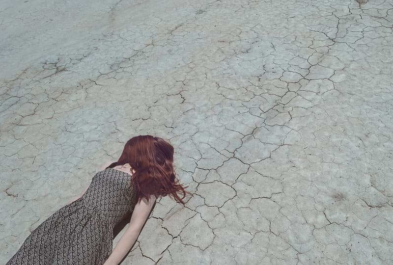 Person in grey and black sleeveless dress lying on grey concrete road