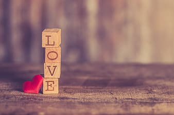 Stacked brown wooden blocks reading love beside red heart pincushion digital wallpaper