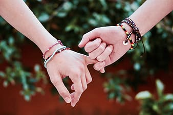 Shallow focus of two person holding hands