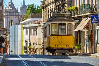 Yellow and white city tram beside buildings