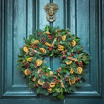 Green, yellow, and red floral wreath hanging on grey wooden door