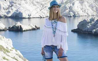 Woman in white off-shoulder long-sleeved shirt and distressed blue denim shorts beside body of water