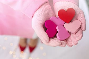 Pink heart shaped ornament on persons hand