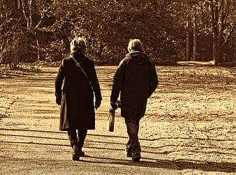 Grayscale photo of man and woman walking on road
