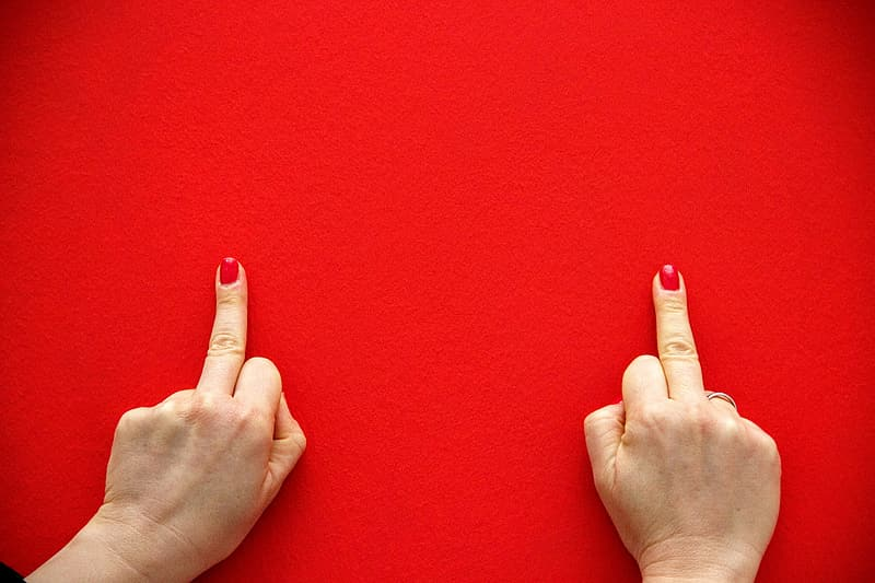 Two human middle fingers on red textile