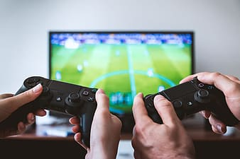 Two friends gaming on PlayStation and television