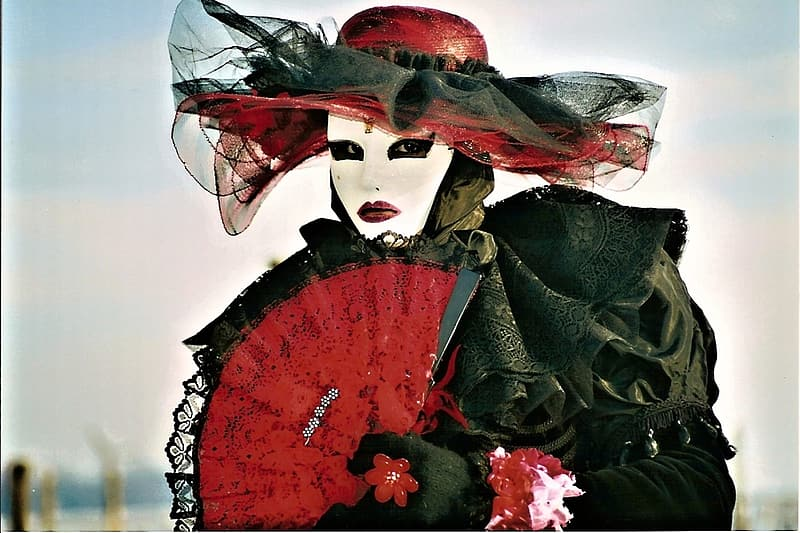 Woman in black dress with red hand fan and red sun hat
