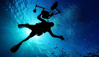 Person wearing diving suit holding camera underwater during day