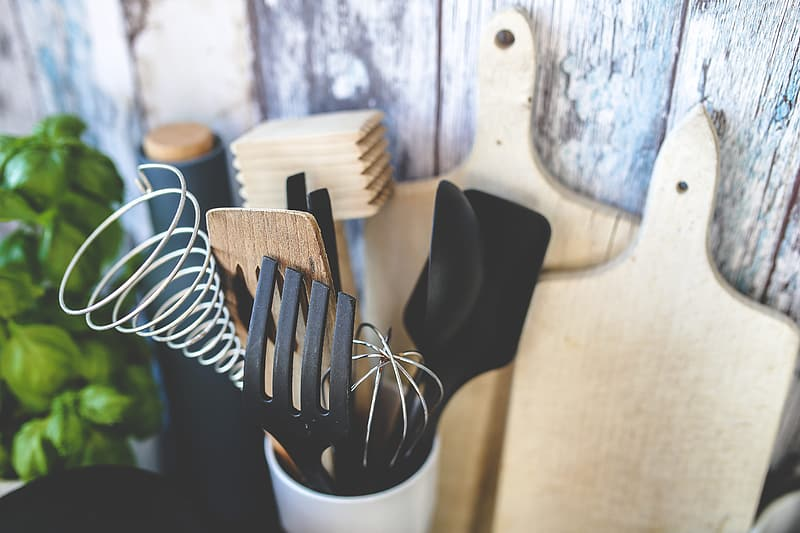 Brown and black kitchen ladles in container