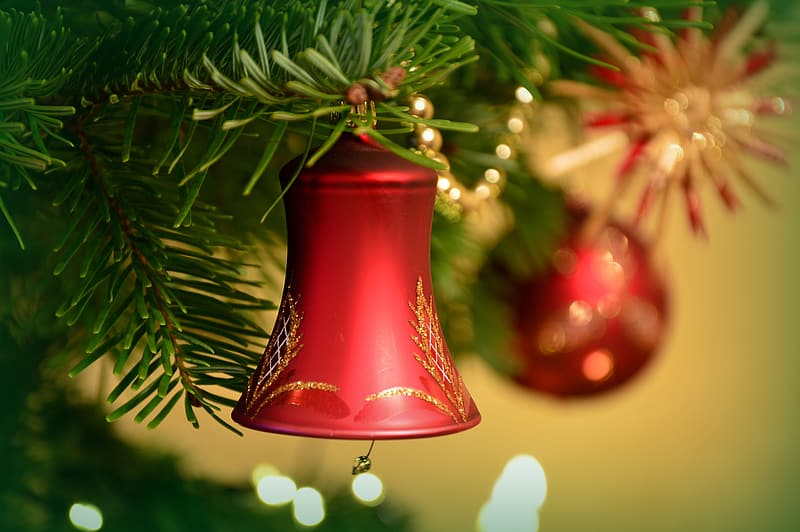 Red bell christmas ornament on green pine tree