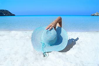 Person holding blue wicker sun hat while laying on white sand during daytime