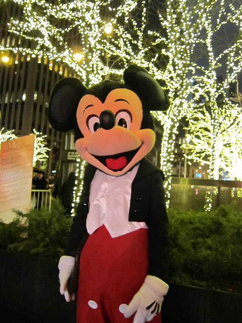 Mickey Mouse mascot in front of LED lighted bare trees