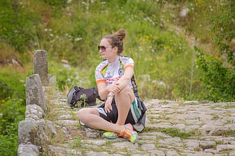 Woman sitting on gray concrete brick pathway near green leafed plants
