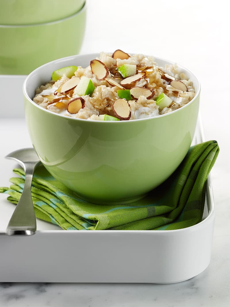 Round green ceramic bowl of cooked food beside silver spoon