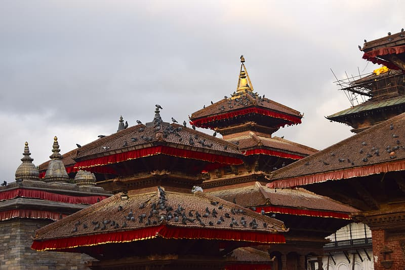 Red and gold temple under white clouds during daytime