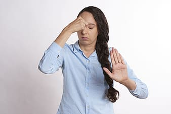 Woman in blue dress shirt covering her face with her hands