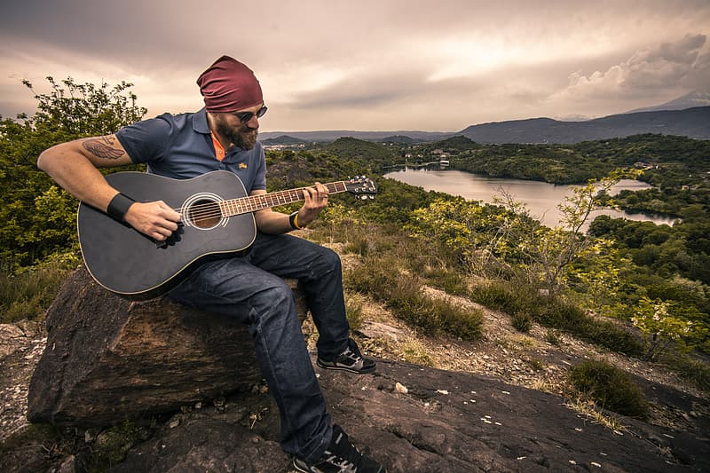 Man playing black acoustic guitar sitting on rock