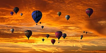 Assorted-color hot air balloons up in sky