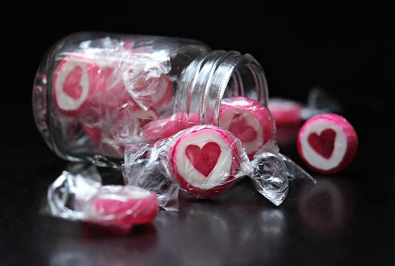 Person taking photo of white-and-pink candies with jar