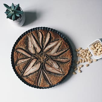 Baked cake near bowl of nuts and succulent plant