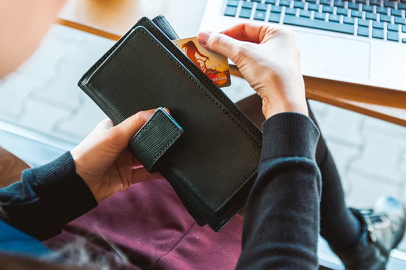 Person wearing black long-sleeved shirt holding black leather long wallet pulling out MasterCard