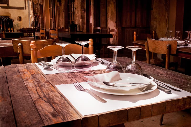 Rectangular brown wooden farm table with plates and wine glasses