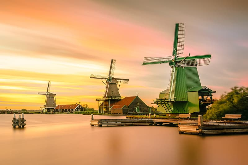 Green windmill near body of water at sunset