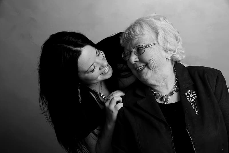 Black haired woman holding white haired woman