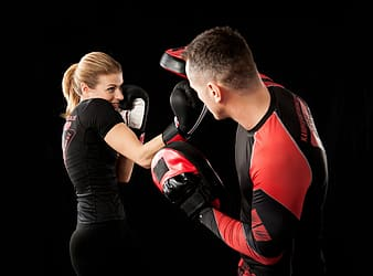 Man in black and red long sleeve shirt and black pants wearing black and red boxing gloves