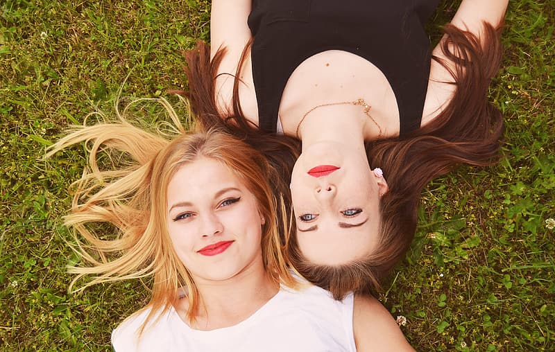 Woman in black tank top lying on grass beside woman in white tank top during daytime