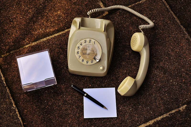 Beige rotary telephone beside white paper and retractable pen