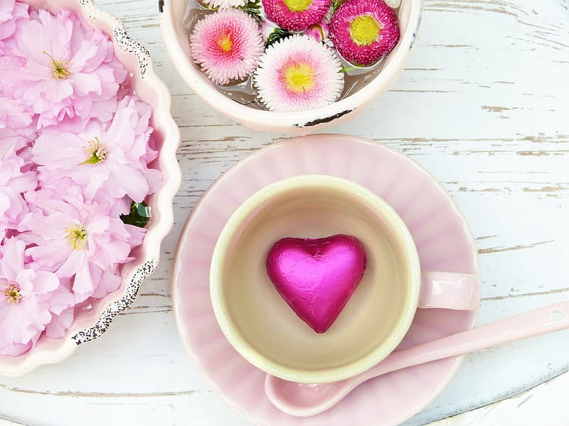 Flowers in bowl beside cup on saucer