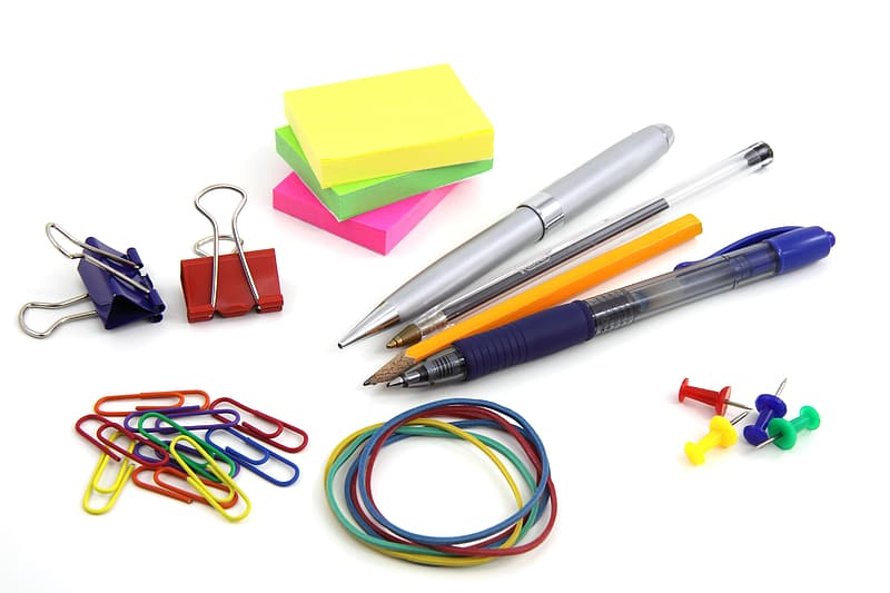 Three pens and yellow pencil beside sticky notes and two binder clips beside paper clips and rubber bands
