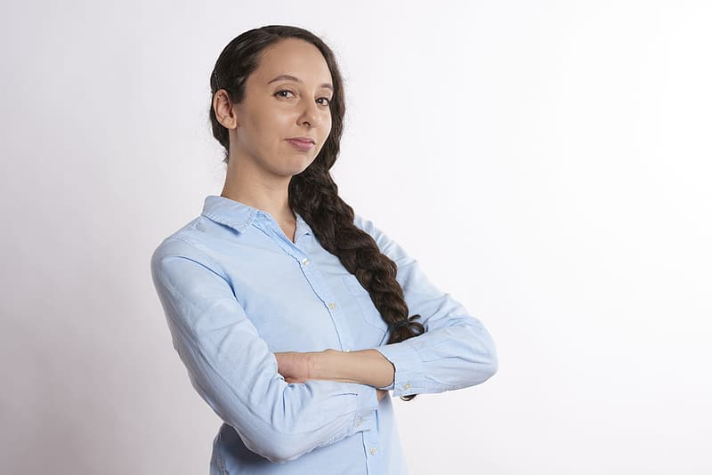 Woman in dress shirt standing with cross hand