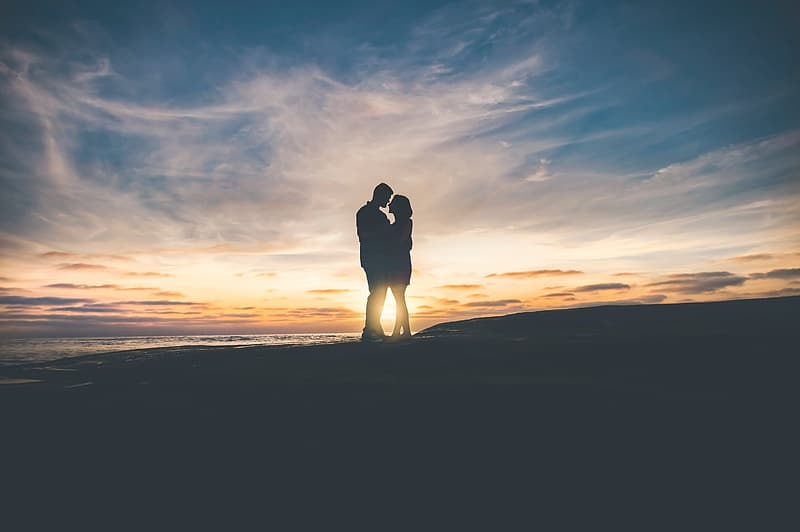 Silhouette of hugging man and woman during golden hour