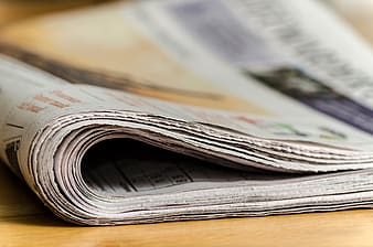 Newspapers on brown wooden surface