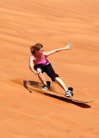 Woman in pink tank top and black pants sand skiing