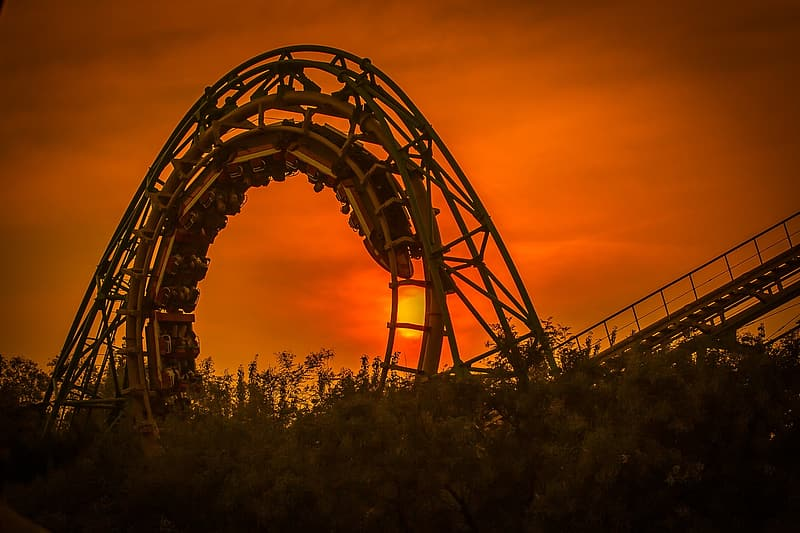 Silhouette photography of round roller coaster rail with roller coaster during golden hour