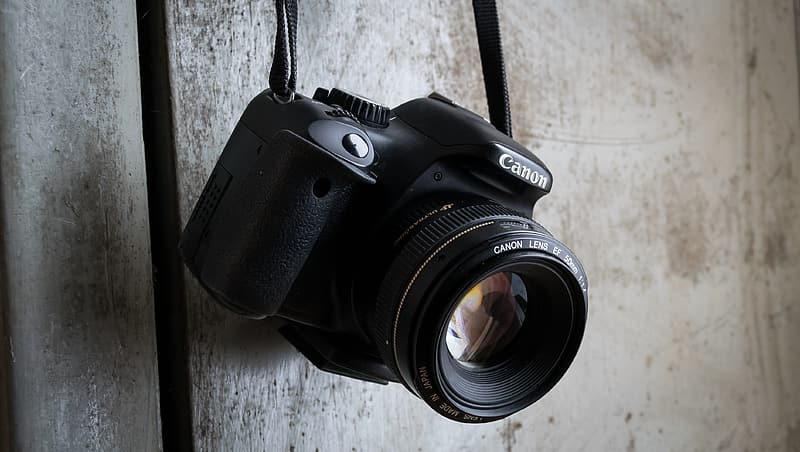 Black Canon DSLR camera hanging on wall