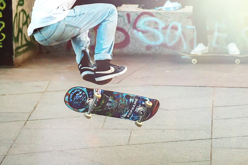 Man playing blue and black skateboard during daytime