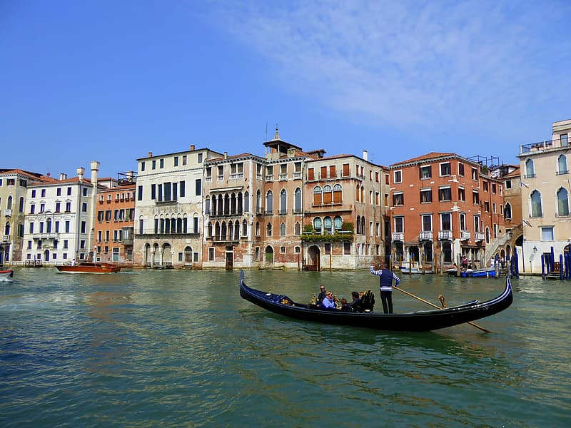 Group of tourist riding gondola on Venice canal