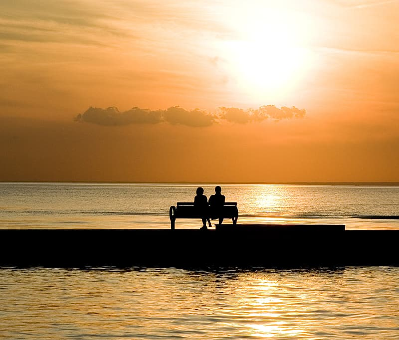 Silhouette of two person sitting on bench near body of water during daytime