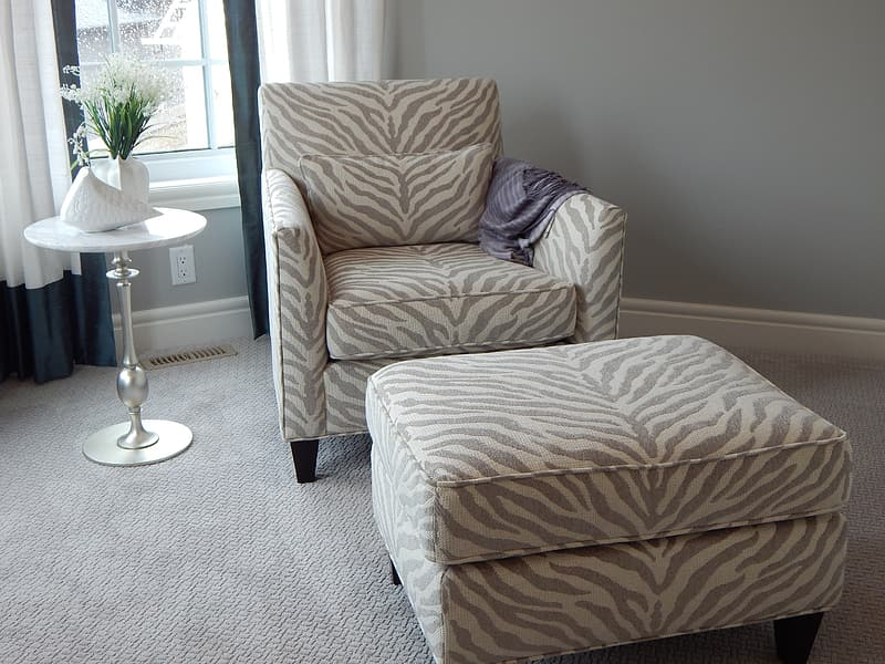 Gray and beige zebra skin printed sofa chair with ottoman beside side table