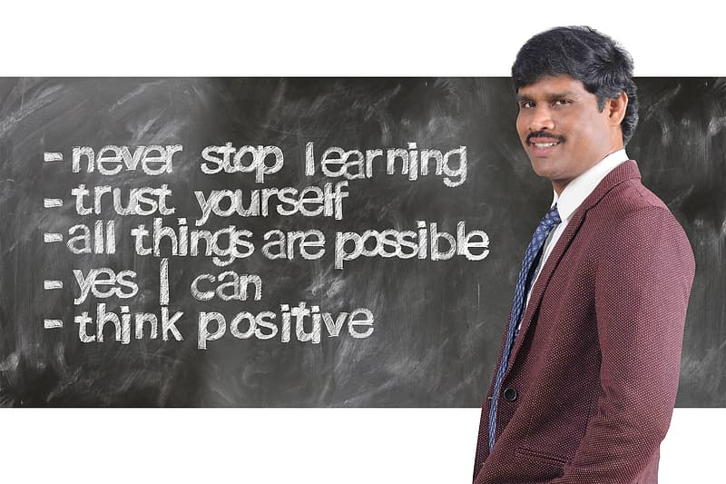 Man wearing maroon suit jacket beside inspirational quote